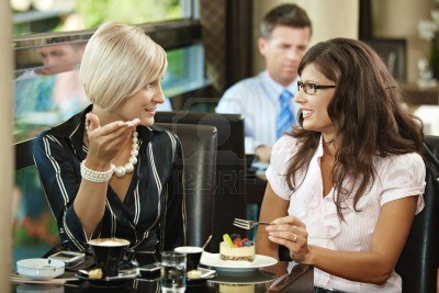 5783692-young-woman-sitting-at-table-in-cafe-drinking-coffee-eating-cake-talking